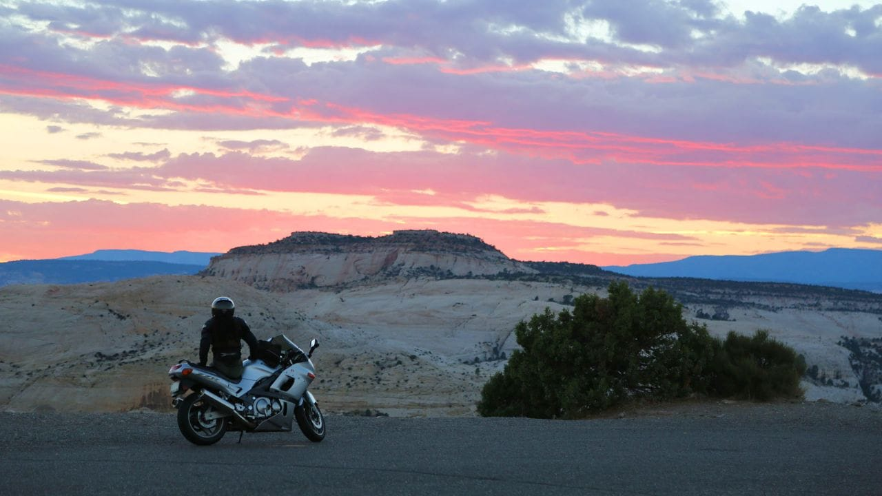 "A motorcycle rider stops to enjoy sunset at ""The Hogback."""