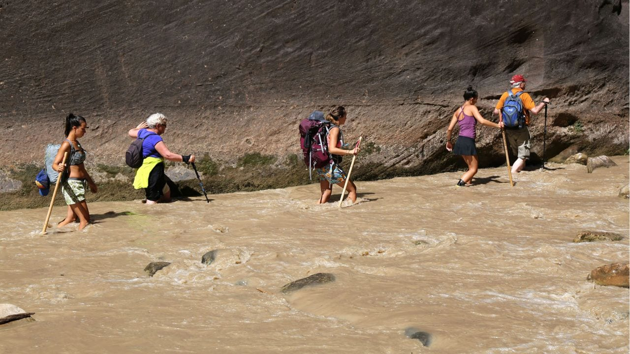 Hikers use walking sticks on a trek through The Narrows.