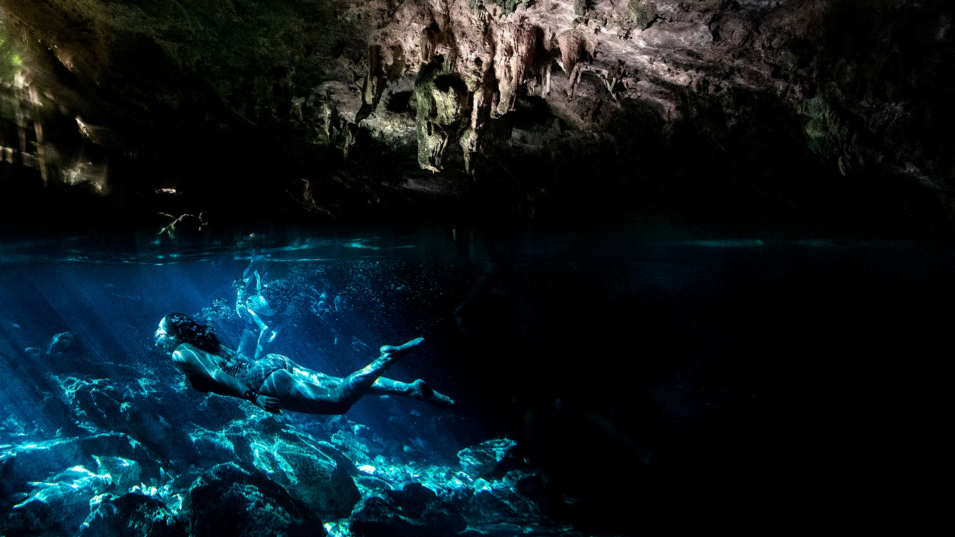 Writer Kassondra Cloos dives through the crystal-clear water at Cenote Dos Ojos.